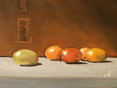 Still life painting showing green, yellow and orange colored Indian berries against the backdrop of a carboard box.