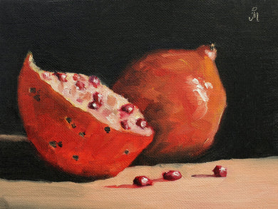 Still life painting showing one half, one full pomegranates and a few arils or kernels in the foreground in dramatic lighting and a dark background.