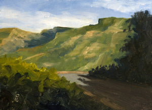 A sunny Landscape painting of blue sky, tall green mountains, a road turning sharply and dark trees in the foreground.
