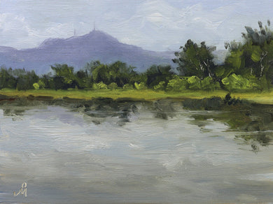 A cloudy landscape painting of a tall blue mountain with a lake and some trees in the foreground.
