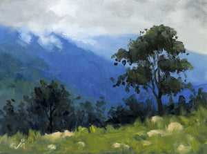 Landscape painting of a tall tree on a gentle slope of a green grassy hill. Clouds partially cover the blue mountains in the background.