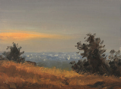 Landscape painting showing an evening scene from a hill overlooking a city. Trees on the hill are seen as silhouettes against gray sky.