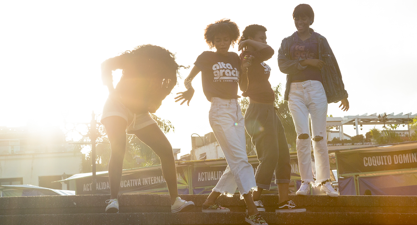 Four friends dance in Alta Gracia gear as the sun sets on the Dominican Republic.