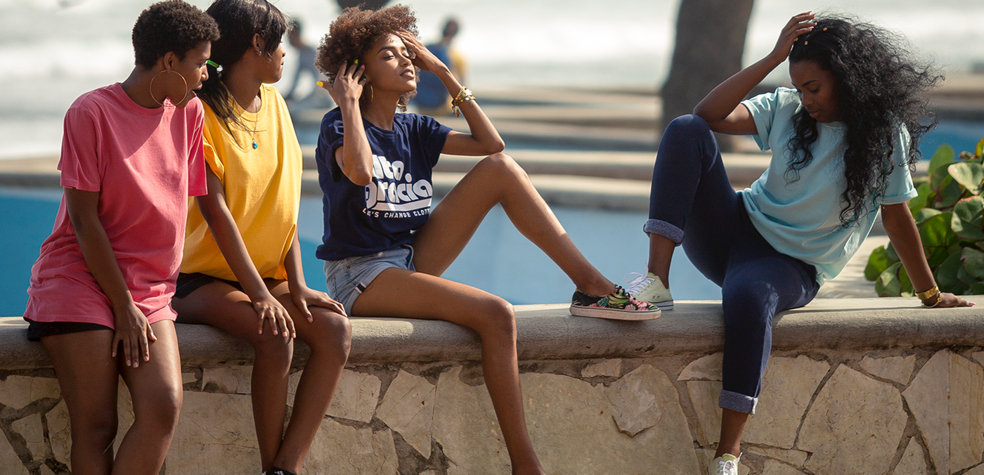 Four friends sit on a ledge chatting in their Alta Gracia tees