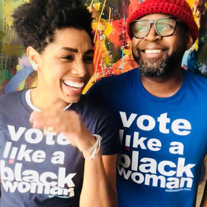 image of two smiling black people, a woman with short hair and a man in a red hat, looking in different directions. text on their shirts reads 'vote like a black woman'