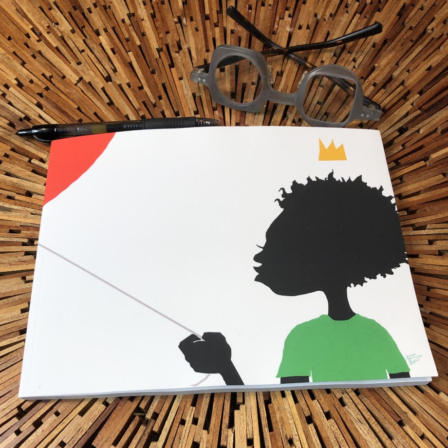 softcover book on wooden table with a pen and pair of glasses.. image on book is a black figure with coily hair, holding a red balloon.