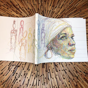 softcover book on wooden table. image on book is a line drawing of the writer ntozake shange, with images of women figures drawn in different colors, to represent the women in her seminal play, 'for colored girls'