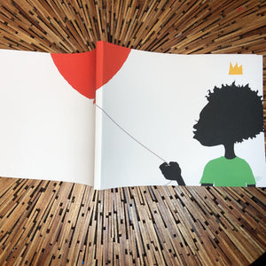 softcover book laying open; artwork on book features the figure of a black child holding a red balloon.