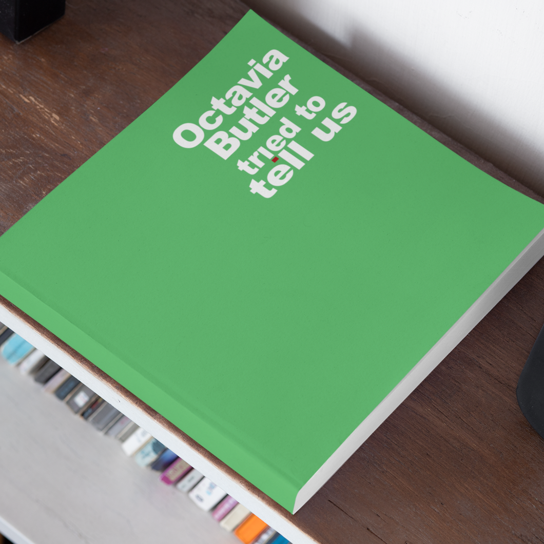 image of green square book sitting flat on wooden bookshelf. text on cover reads,
