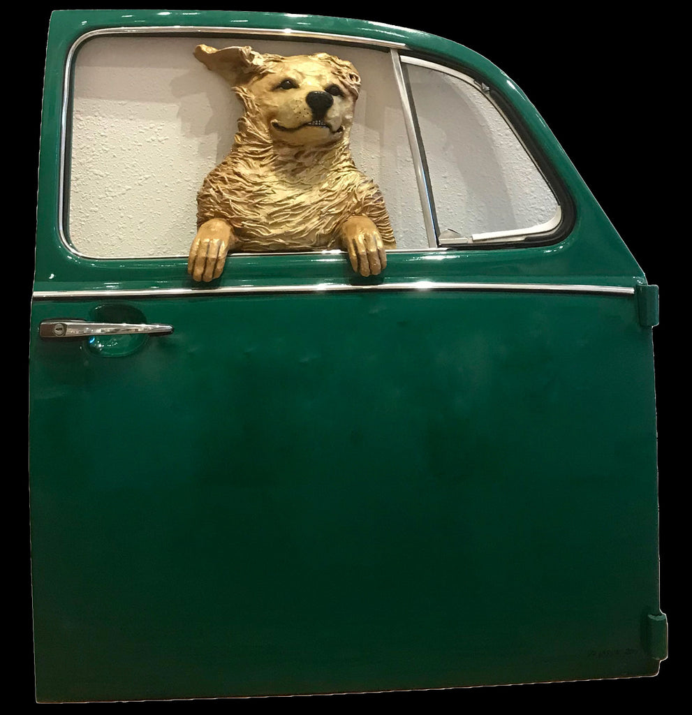 Golden dog in a green Volkswagen door