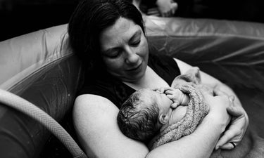 SNOO story: Victoria David - mother cradling baby after homebirth