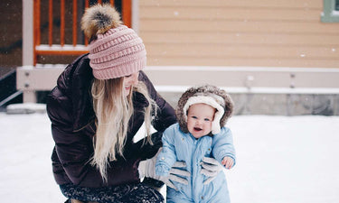 Cold weather tips for babies and toddlers - bundled up baby playing in snow with momr