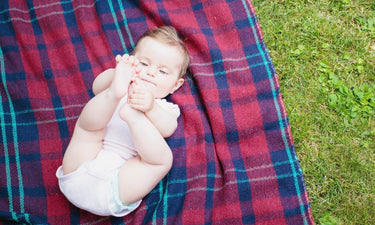 Baby girl laying on tartan blanket and grabbing at her feet.