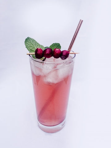tall glass with gingerale, cranberry juice, copper straw and skewered cranberries and mint leaves.