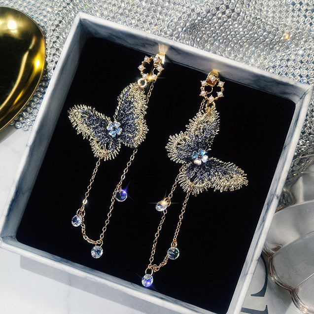 Dangly gold and sapphire colored butterfly drop earrings.