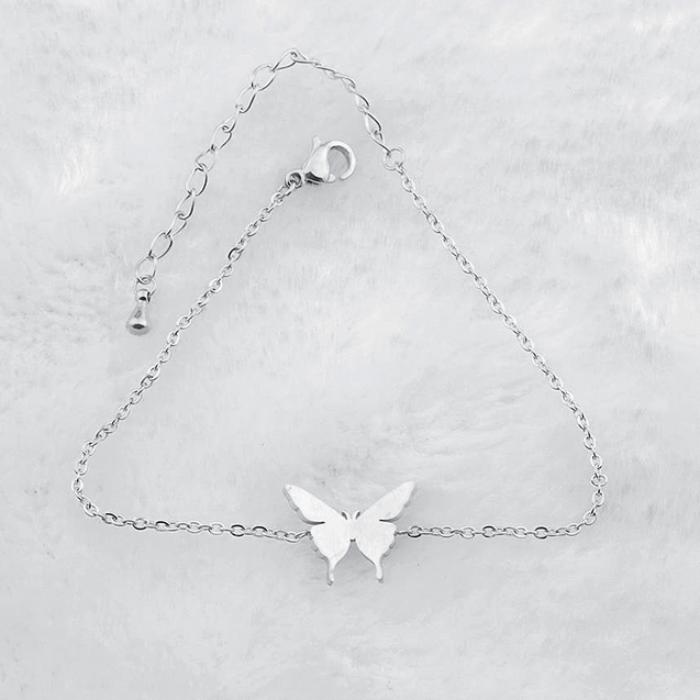 Silver butterfly charm bracelets on marble background.
