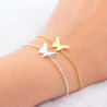 Silver and gold butterfly charm bracelets on wrist.