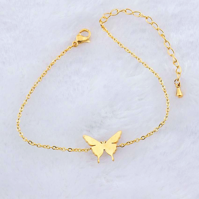 Gold butterfly charm bracelets on marble background.