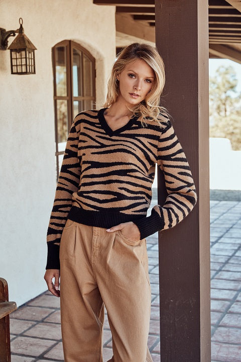 Womna wearing animal print swater and brown trousers