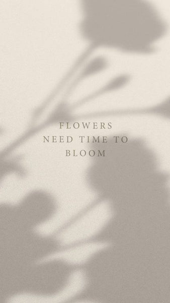 """Image of tan wall with flower shadows.  Text on wall says """"Flowers need time to bloom."""""""