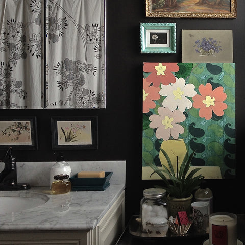 Shannon Kaye grouped all kinds of floral art pieces in a bathroom on an off black wall for quirky impact and fresh color