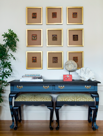 Shannon Kaye painted the cabriolet console table with horizontal stripes then topped the piece with a beautiful display of Buddhist prayer cards for a geometric vignette that equals elegance