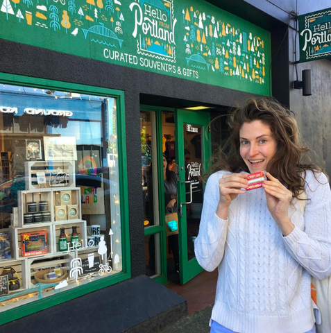 Elena holding a lip balm in front of a Portland gift shoppe