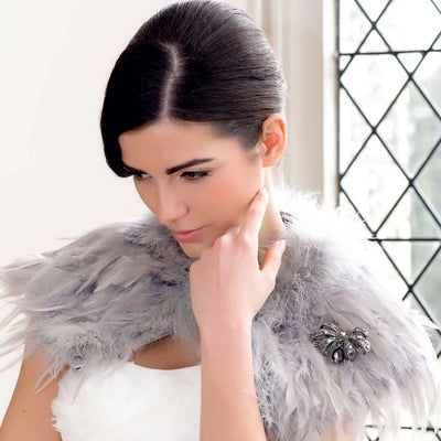 Model bride wears Bow of Drama Brooch in a fur shrug