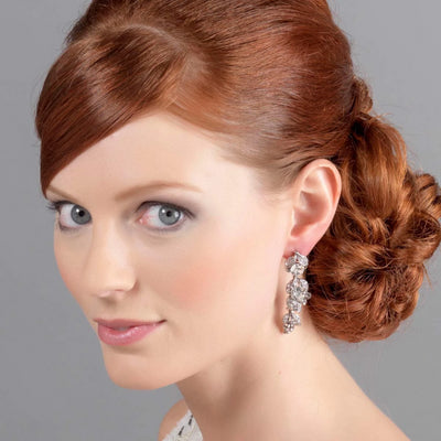Vintage Treasure drop earrings shown on our model bride with a side chignon hairstyle