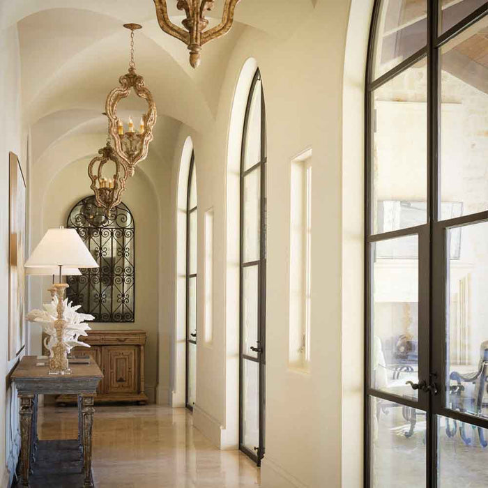 This California Spanish style home features a beautiful Groin Vault Ceiling flanked by arched doors and accented with wrought iron details