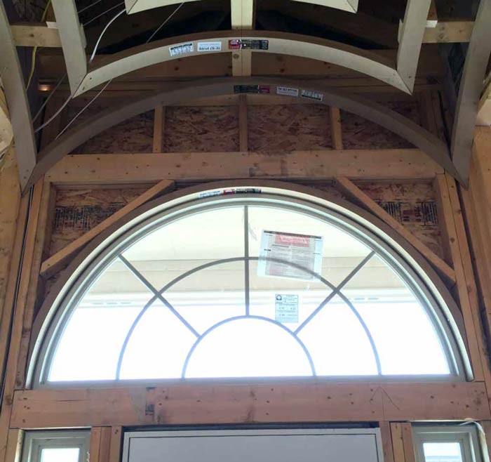 Fan-shaped arched window being framed above a front door under a groin vault