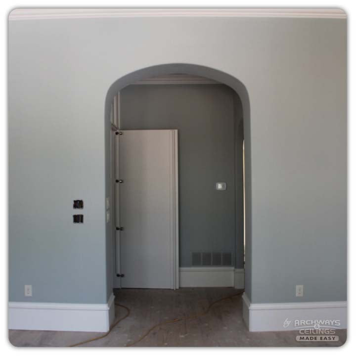 An arched hallway after framing and drywall