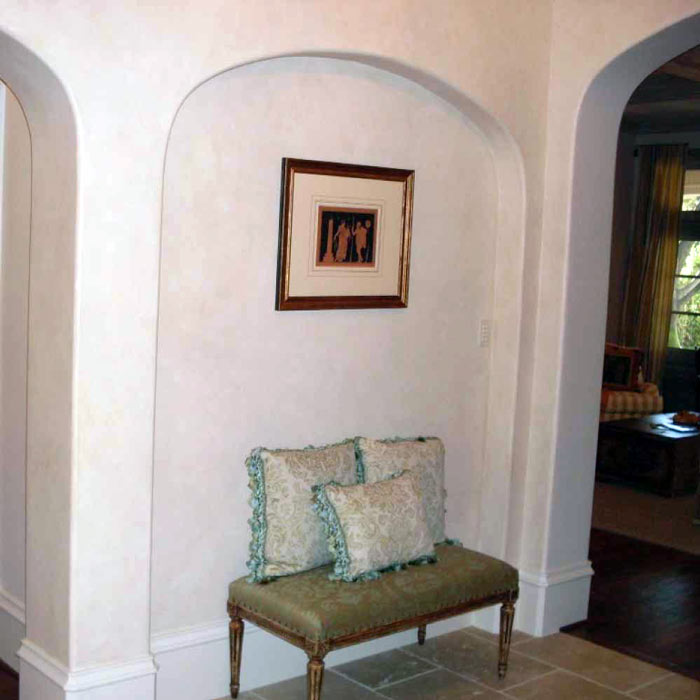 A large wall niche with a soft arch serves as a functional and decorative element for Federal-style home design