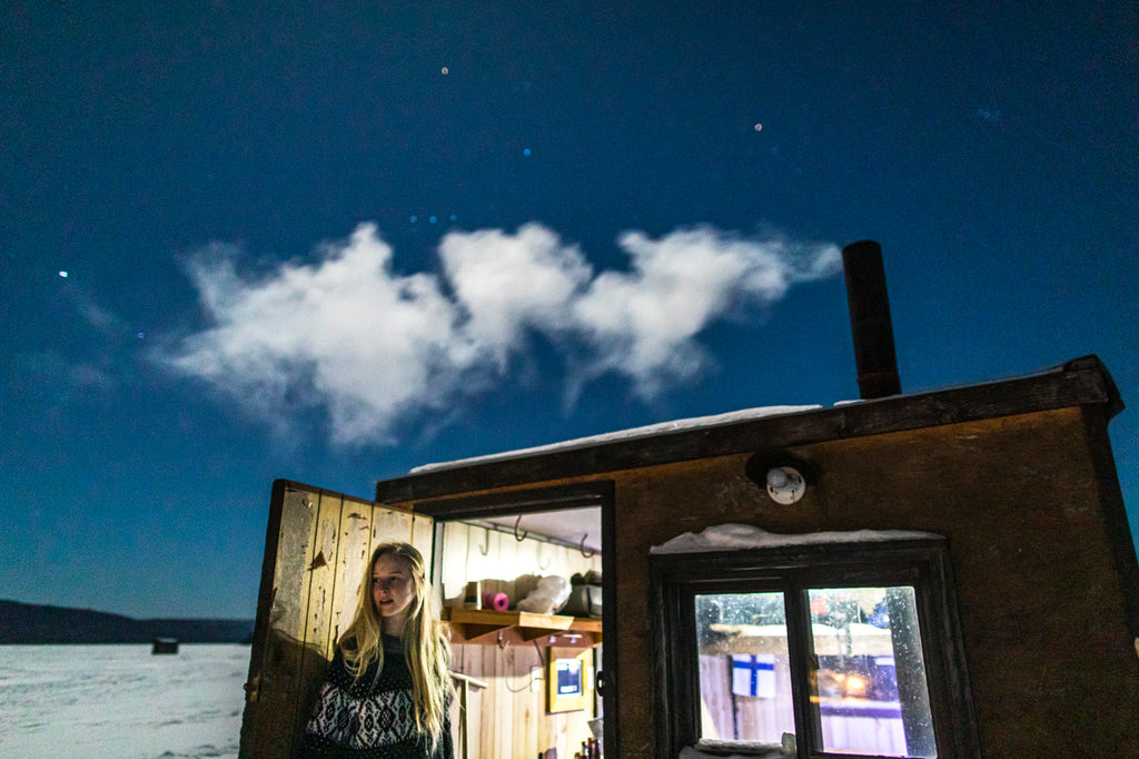 woman looking out from an ice hut under satrry sky - photo david Jackson