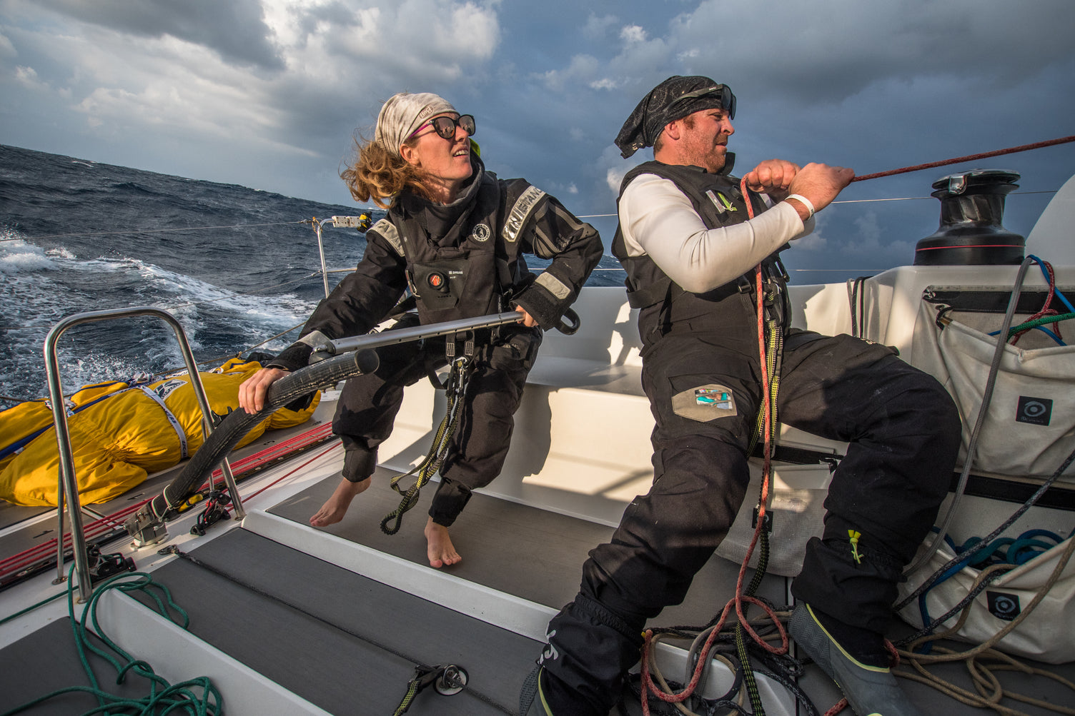 man and women adjust the sails of their racing sail boat