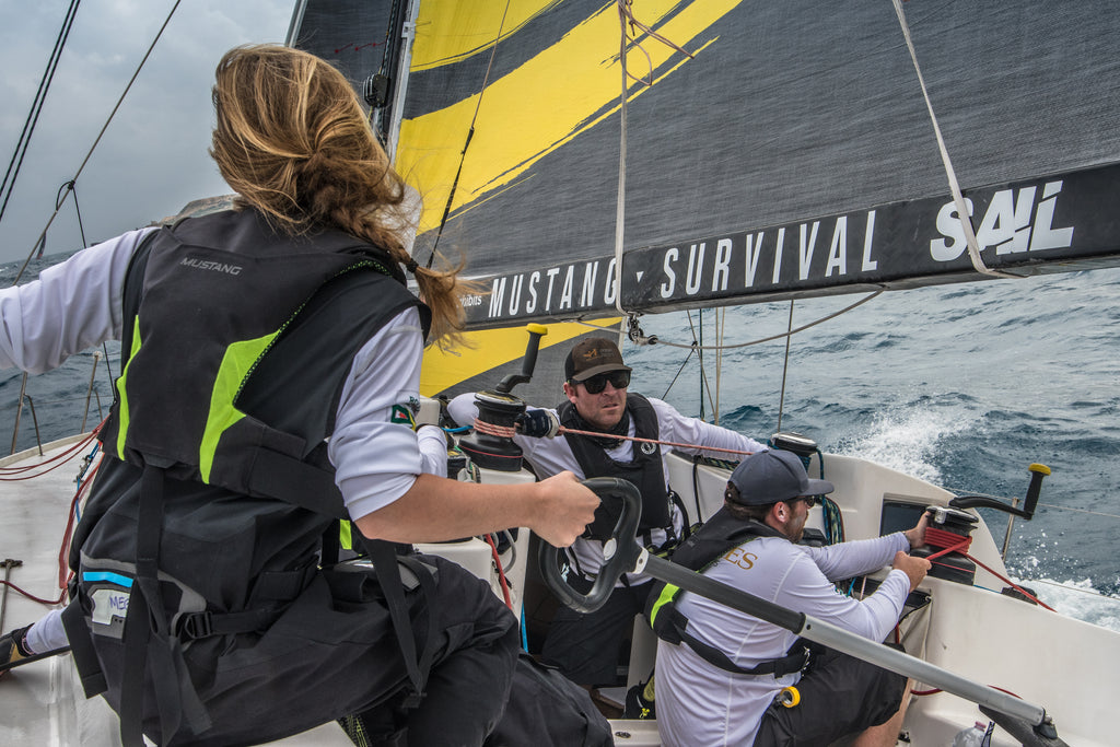 back of young women at helm of ocean racing yacht at full sail