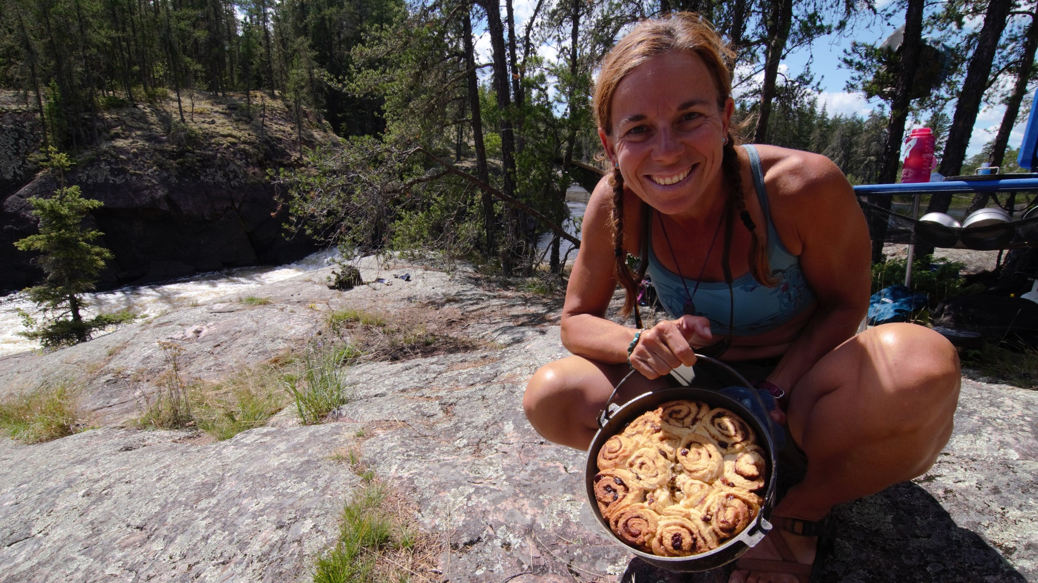 womanoutside crouched on a rock holding out a dutch oven full of cinnamon buns made while camping