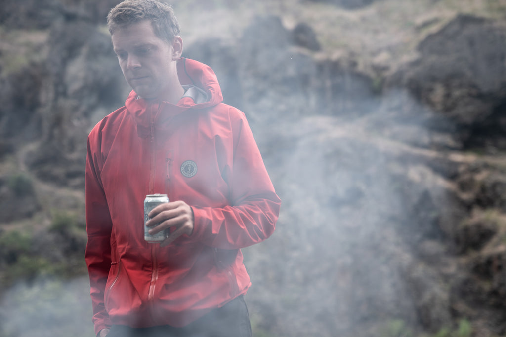 young man in red waterproof jacket by smoke of evening camp fire