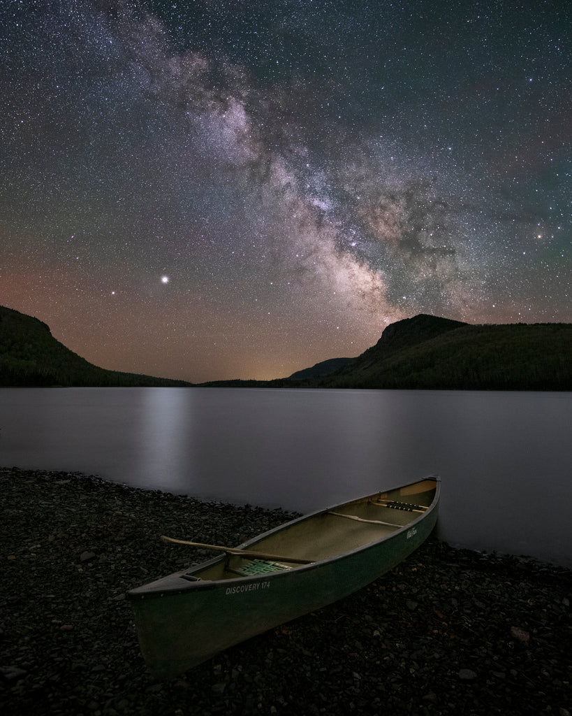 canoe on shore under starry moonlight sky