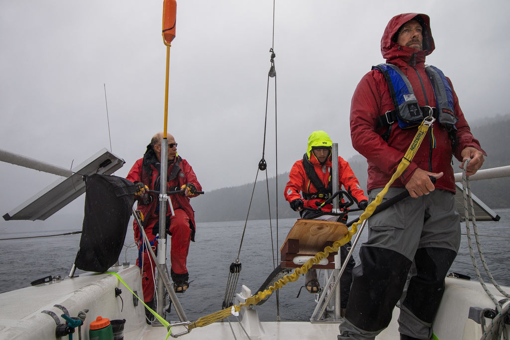 three men in foul weather gear on sail boat. two at back are peddling