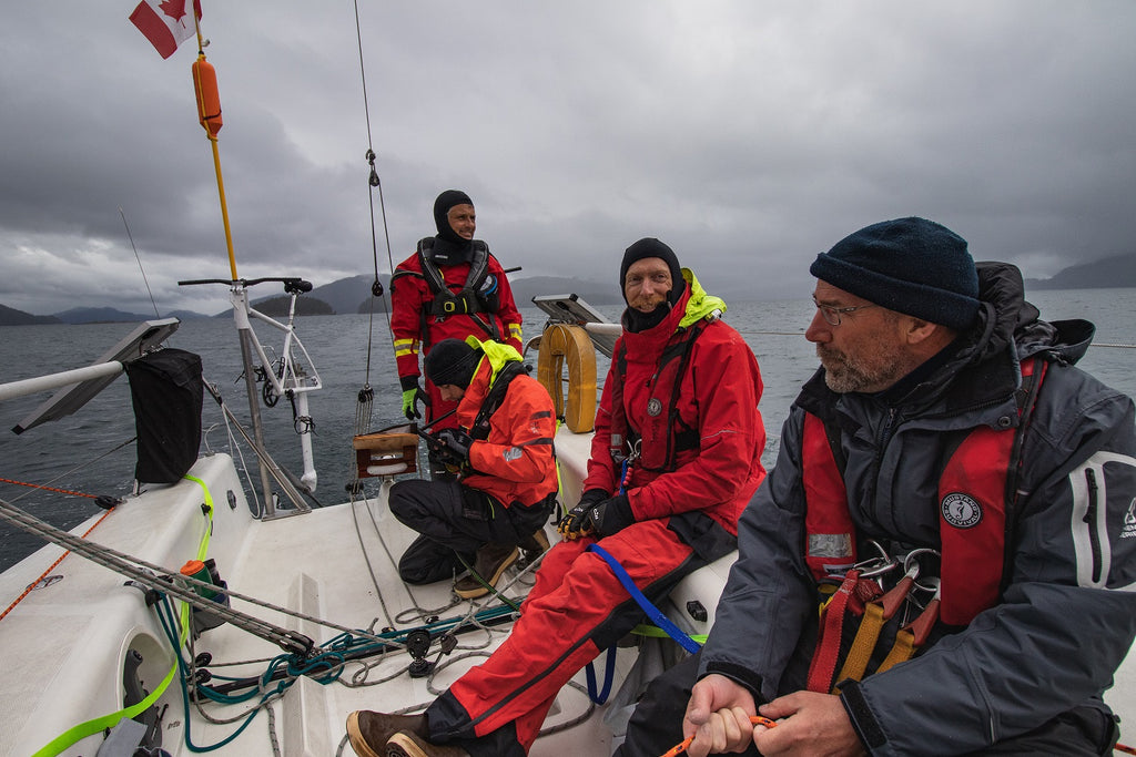 three men in foul wether gear on deck of sailing boat on cloudy day