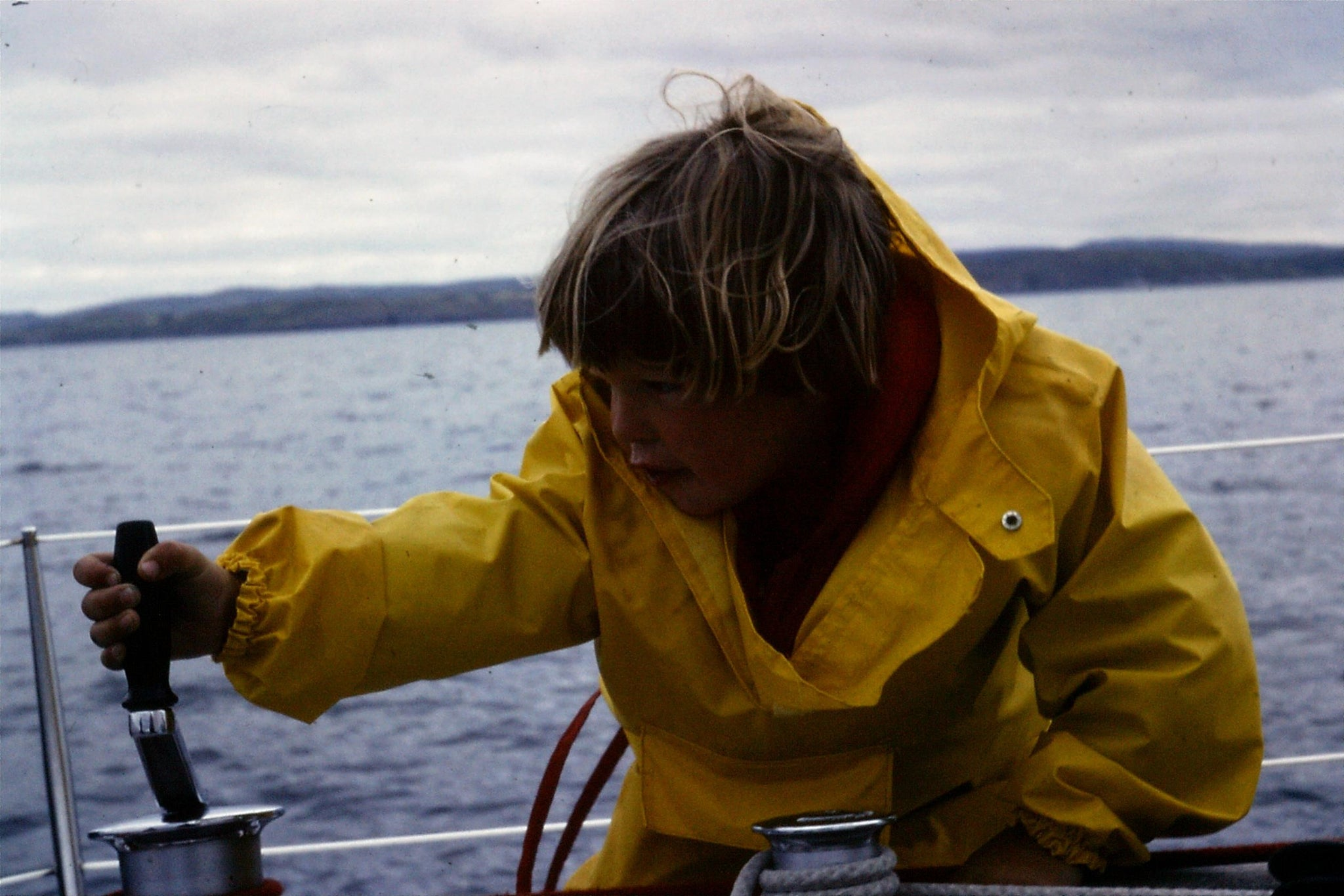 child in yellow rain gear on sailing boat