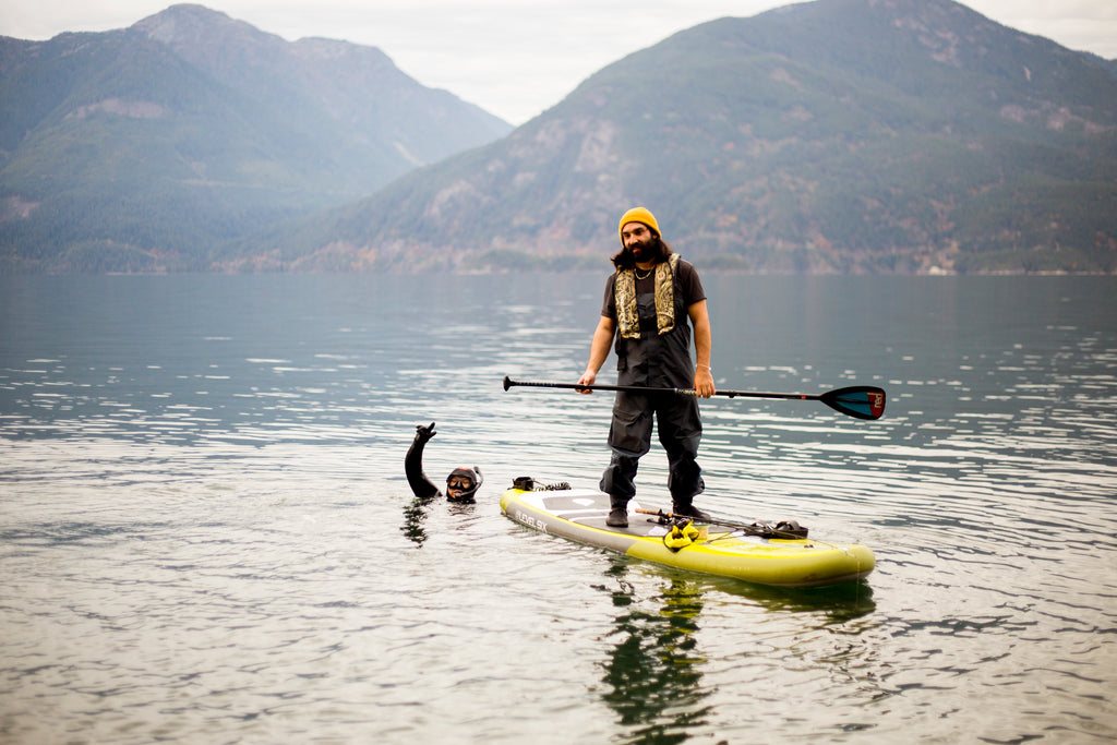 man fishing from a paddle board in how sound BC with diver next to him