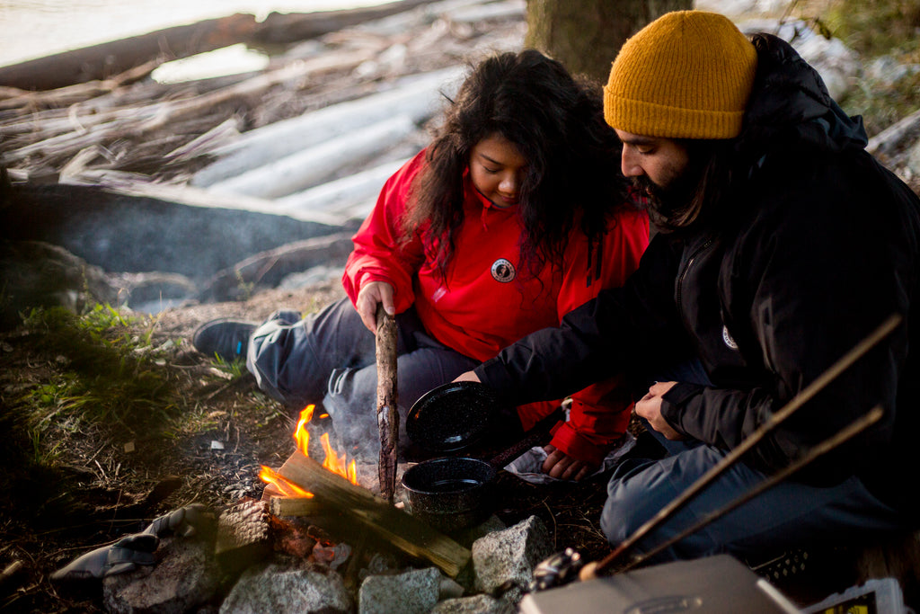 young couple in waterproof jakets cooking over open camp fire by the water