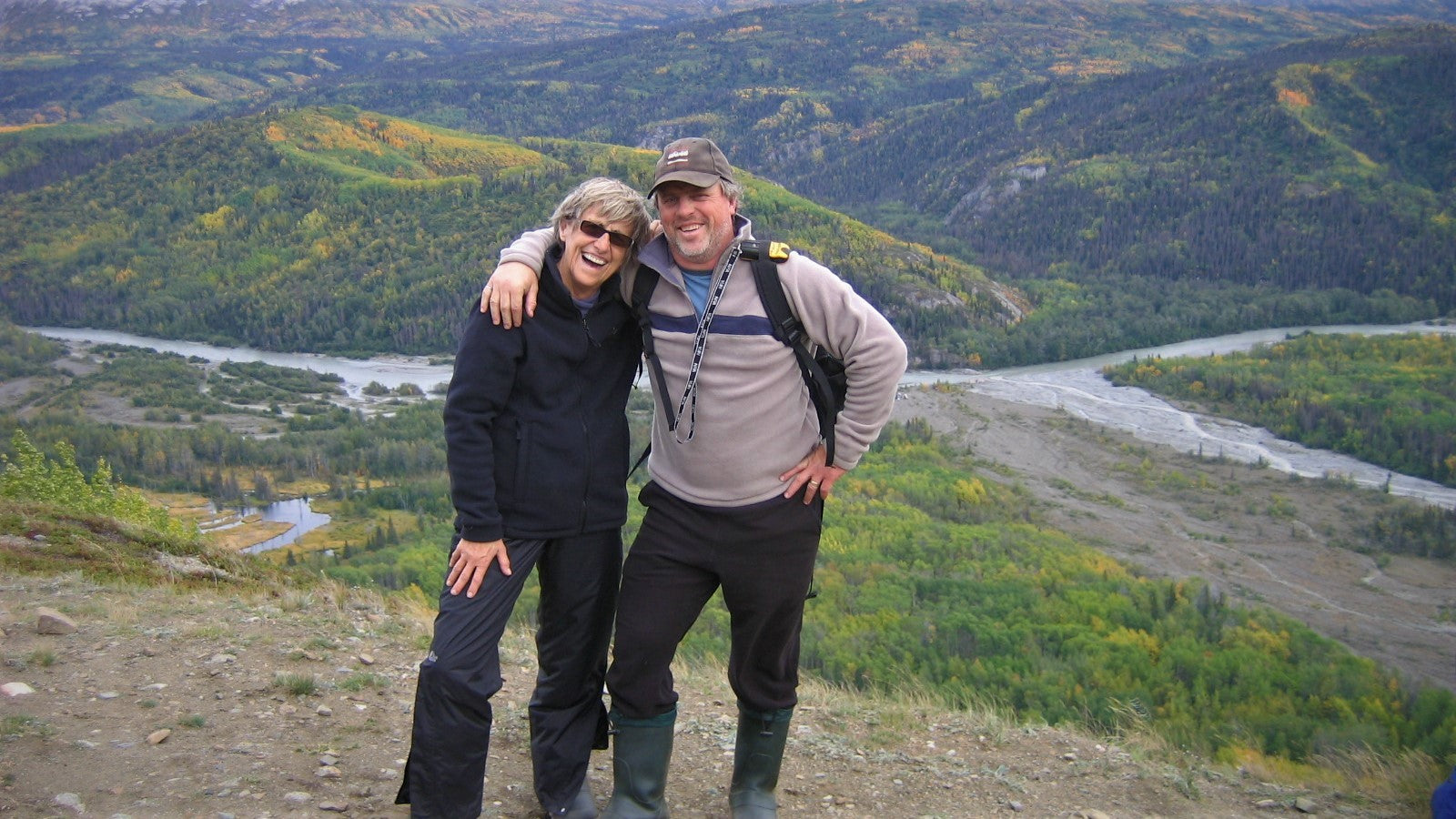 mother and son smiling atop a mountain