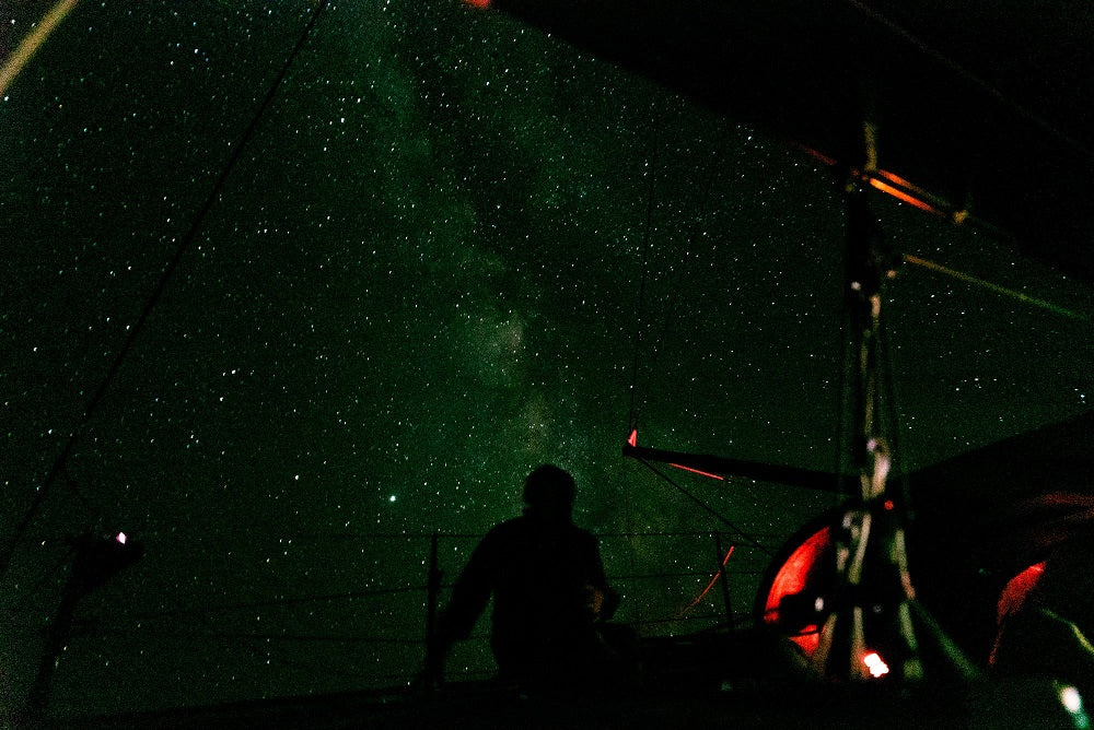 woman gazing up at night sky full of stars from aboard a sail boat
