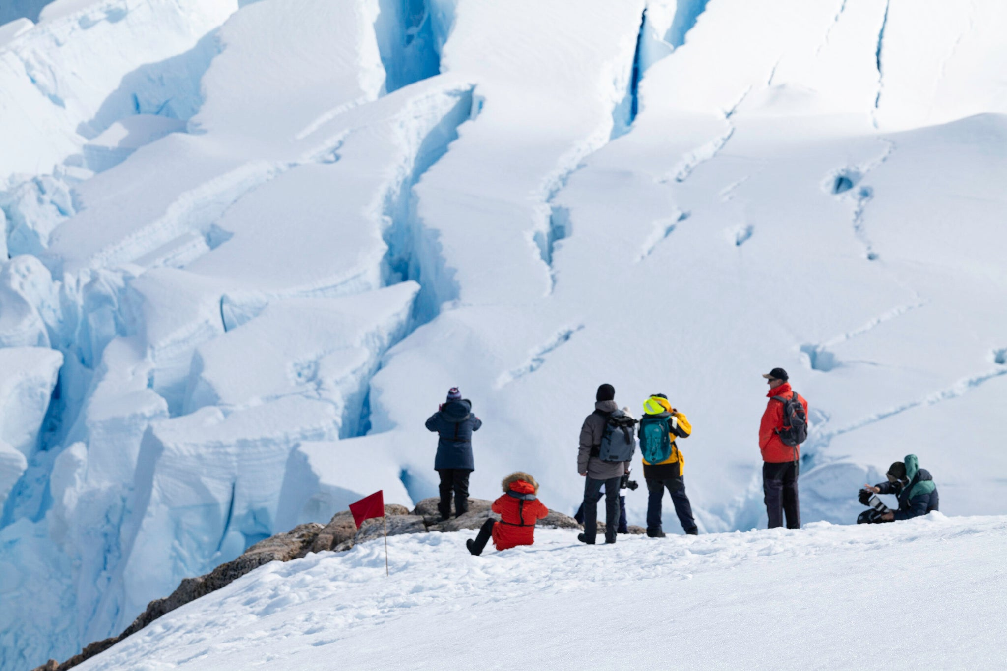 people standing on a glacier, 2.	Looking down into the crevasses of the creeping glacier at Neko Harbour, Antarctic Peninsula.