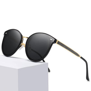 circle sunglasses with black lens color, gold nose bridge and temple arms