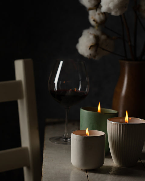 Three ceramic candles burning in winter light with glass of red wine on country pine table