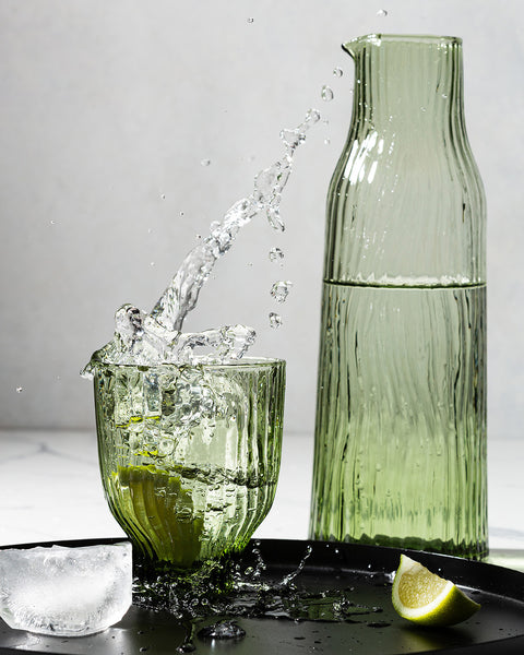Large coloured green glass crystal. glass and tumbler with splashing liquid overpouring from the tumbler